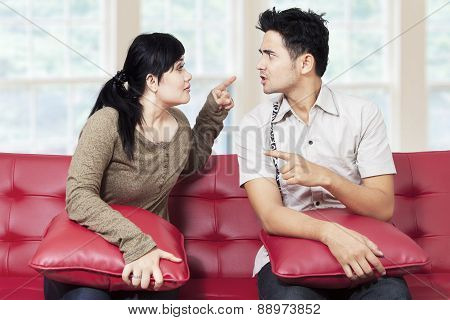 Couple Quarreling While Sitting On Sofa