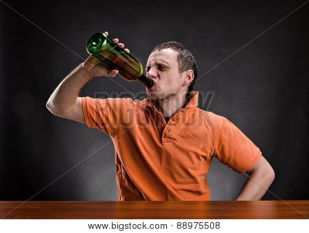 Man drinks alcohol over gray