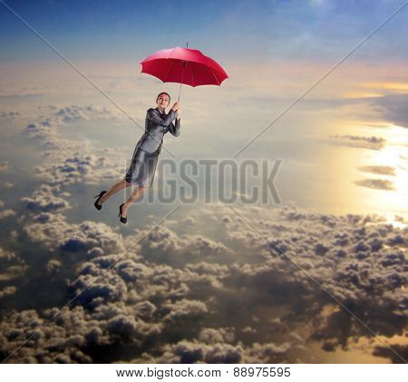 Woman flying in the sky with umbrella