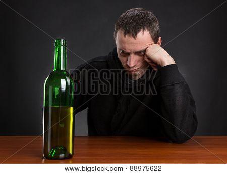 Sad man looks at the bottle