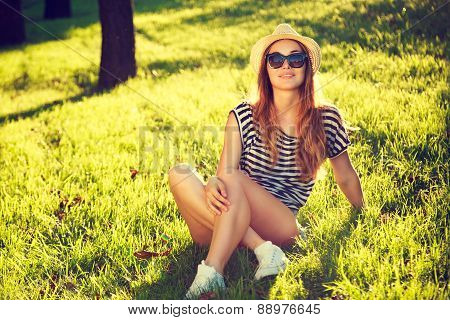 Happy Hipster Girl Relaxing on the Grass