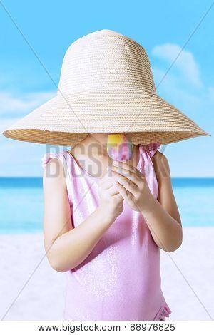 Kid With Hat Enjoy Ice Cream At Shore