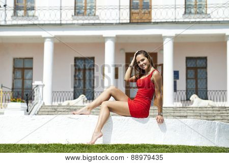 Beautiful young girl in a short red dress sitting on the white stone