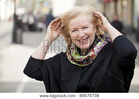 Happy portrait of an elderly blonde woman, spring on the street