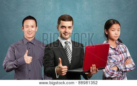 Team and male businessman in suit with laptop in his hands, looking on camera