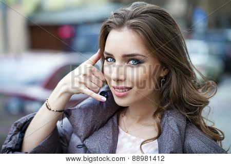 Beautiful woman making a call me gesture, outdoors in spring