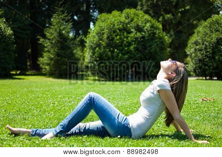 Young smiling woman relaxing on the grass