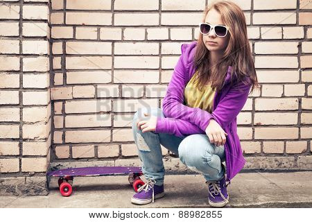 Blond Teenage Girl In A Sunglasses With Skateboard Sits