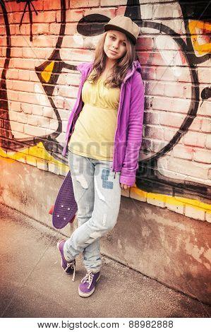 Blond Beautiful Teenage Girl In Cap Holds Skateboard