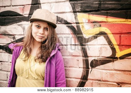 Blond Stylish Teenage Girl Stands Near Urban Wal