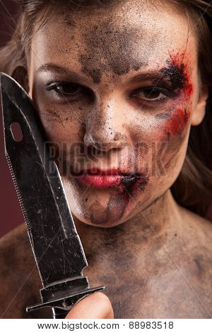 Sexy girl holding a knife. Woman with blood on face.