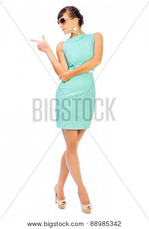 Glamorous girl in turquoise dress shows pointing gesture isolated