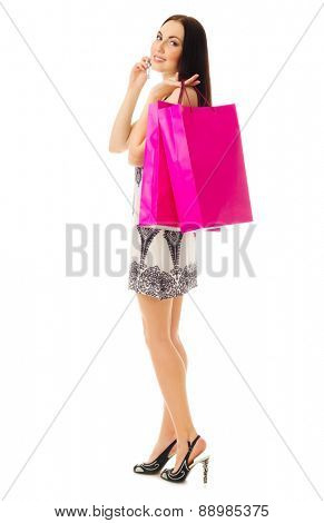 Young girl in black and white dress with bags talks by mobile phone isolated