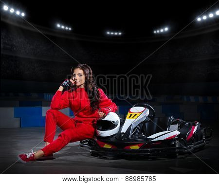 Young girl racer with kart at stadium