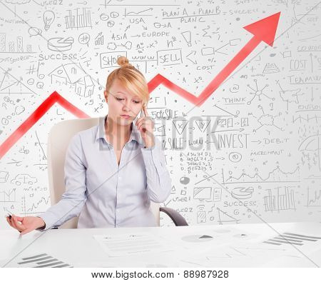 Business woman sitting at table with market hand drawn diagrams