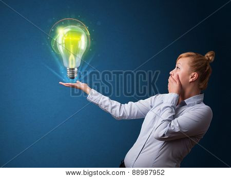 Young businesswoman holding glowing lightbulb in her hand