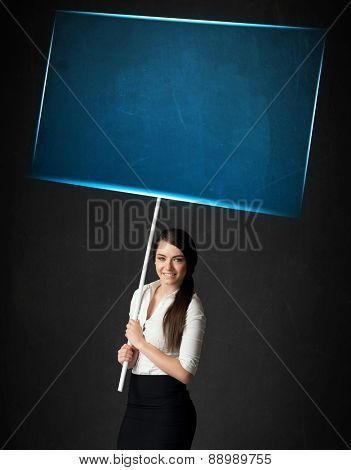Young businesswoman holding a big, blue board