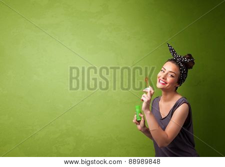 Beautiful woman blowing soap bubble on copyspace green background