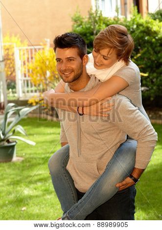 Man giving piggyback ride to girlfriend outdoors, smiling.