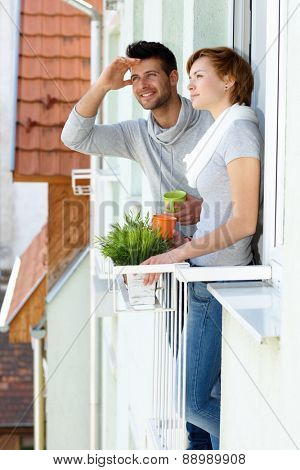 Young couple standing at balcony, having coffee.