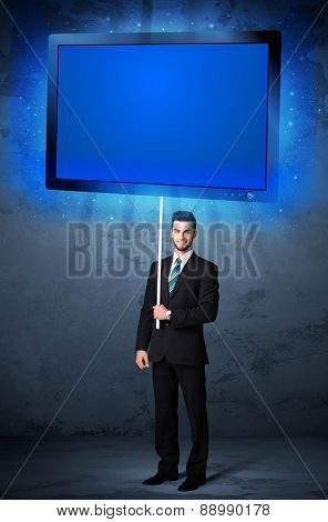 Young businessman holding a big, blue shining tablet