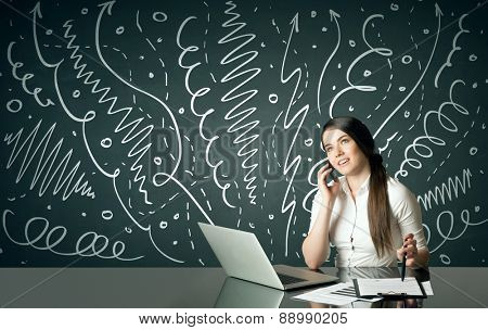 Businesswoman sitting at table with drawn curly lines and arrows on the background