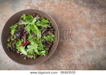 A Bowl Of Fresh Mixed Green Salad On Metal Textured Background