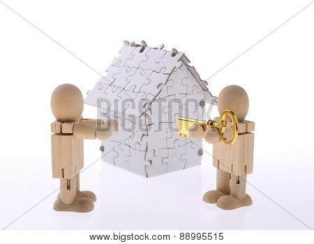 House from puzzle  with a key on a hand