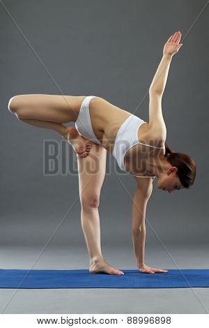 Flexible woman exercising yoga in studio