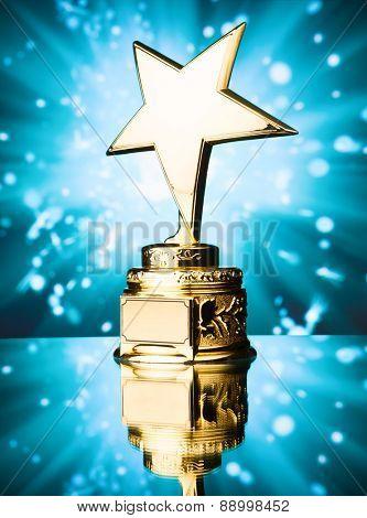 gold star trophy against blue sparks background