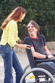 image of rollator  - girl is talking to a handicaped boy on a wheelchair - JPG