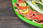 image of redfish  - Large Dish With Fresh Stuffed Fish Salmon Steaks Lemon Slice And Herbs - JPG