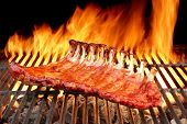 foto of bbq party  - BBQ Baby Back Spicy Marinated And Smoked Pork Ribs On The Hot Charcoal Grill With Bright Flames On Black Background - JPG