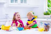 foto of healthy eating girl  - Little girl and boy preparing breakfast in white kitchen. Healthy food for children. Child drinking milk and eating fruit. Happy smiling preschooler kids enjoying morning meal cereal banana and strawberry.