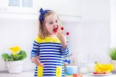 picture of healthy eating girl  - Little girl preparing breakfast in white kitchen. Healthy food for children. Child drinking milk and eating fruit. Happy smiling preschooler kid enjoying morning meal cereal banana and raspberry.