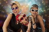 image of rockabilly  - Rockabilly woman with her tow daughters having fun posing with vintage microphone in 1950 - JPG