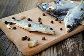 stock photo of cod  - Salty stockfish cod on wooden board with gaarlic and pepper - JPG