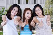foto of school building  - Beautiful teenage girls standing in front of school building and showing thumbs up together - JPG