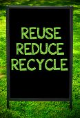 stock photo of reuse recycle  - REUSE REDUCE RECYCLE message on sidewalk blackboard sign against green grass background - JPG