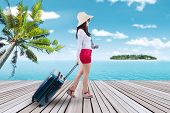 stock photo of carry-on luggage  - Portrait of female tourist walking on the pier while carrying a suitcase to the island resort - JPG