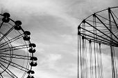 stock photo of amusement  - Silhouettes amusement Park on background of blue sky - JPG
