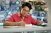 picture of calculator  - Young asian entrepreneur owning a computer shop and checking bills and invoice with calculator doing budget and reviewing taxes - JPG