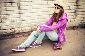 stock photo of snickers  - Blond teenage girl in jeans cap and sunglasses sits on her skateboard near urban brick wall photo with warm retro tonal correction effect instagram old style filter - JPG