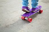 picture of snickers  - Riding skateboarder feet fragment in jeans and gumshoes - JPG