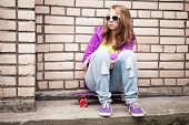 foto of snickers  - Blond teenage girl in a sunglasses with skateboard sits near urban brick wall photo with retro tonal correction instagram old style filter - JPG