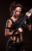 pic of sniper  - Sniper woman in leather sexy wear. Riot woman with gun on dark background