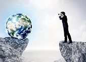 "stock photo of top-gun  - Businessman standing on the edge of mountain with a globe on the other side, """"Elements of this image furnished by NASA""""  - JPG"