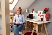 stock photo of lap  - Young woman sitting in chair at home - JPG