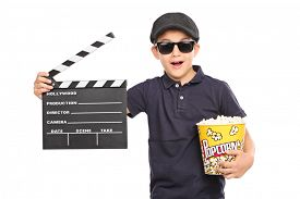 stock photo of beret  - Little kid with a beret and sunglasses holding a box of popcorn and a movie clapperboard isolated on white background - JPG