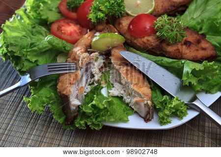 A Piece Of Fried Fish Fillett Served On Blue Glass Table With Lettuce, Lime, Tomato And Herbs